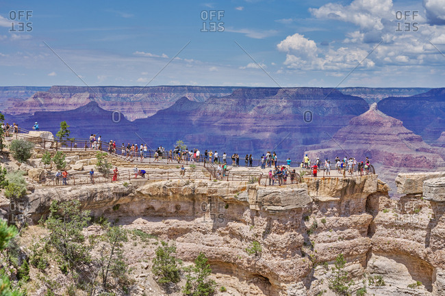 Grand Canyon National Park, Arizona - August 4, 2019: Tourists on lookout cliff overlooking canyons