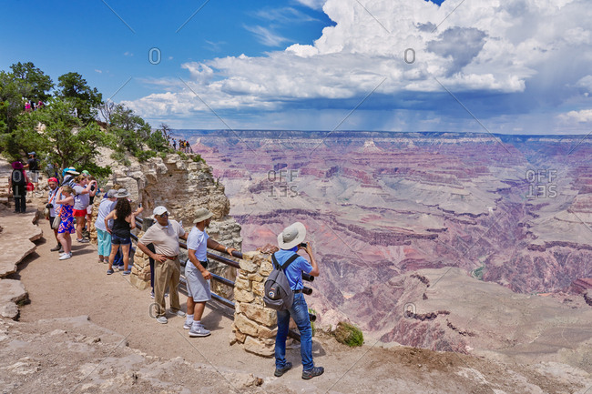 Grand Canyon National Park, Arizona - August 4, 2019: Tourists standing on cliff overlooking canyons