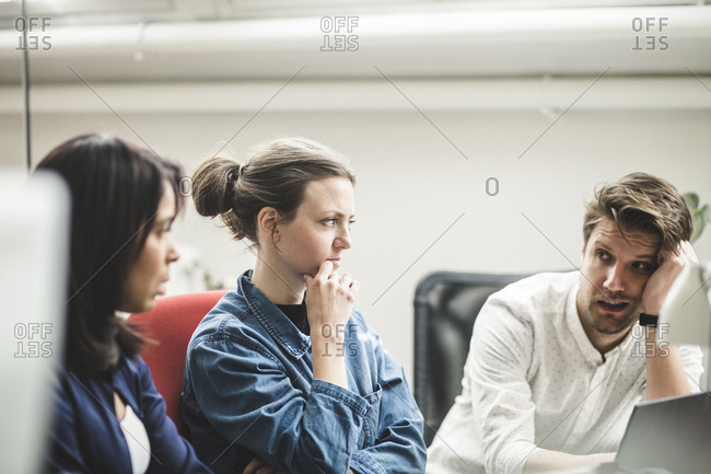 Businessman discussing with female professionals in meeting at creative office