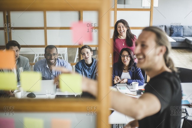Smiling colleagues looking at businessman explaining strategy in meeting seen through glass wall