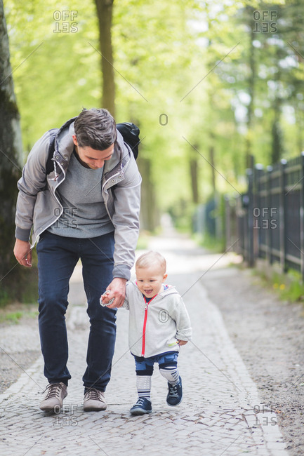 Full length of father and son holding hands while walking on footpath
