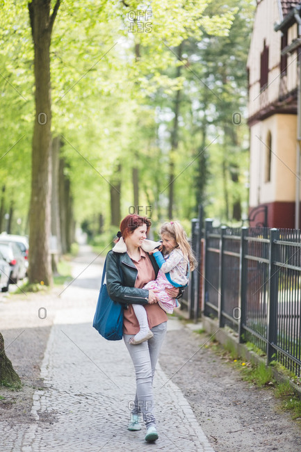 Happy mother carrying daughter while walking on footpath