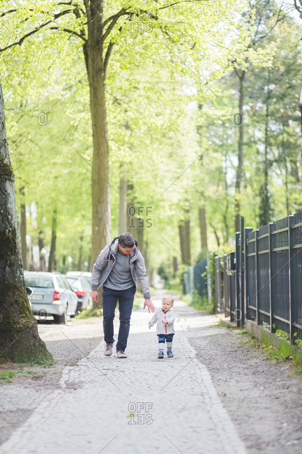 Full length of father with son walking on footpath