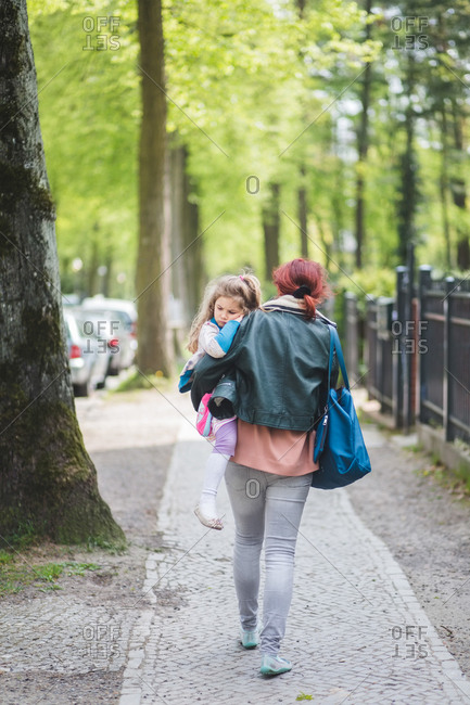 Rear view of mother carrying daughter while walking on footpath