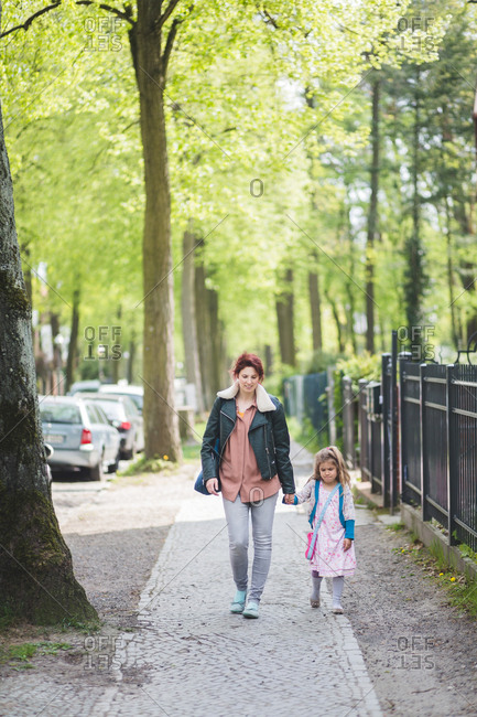 Full length of mother and daughter holding hands while walking on footpath