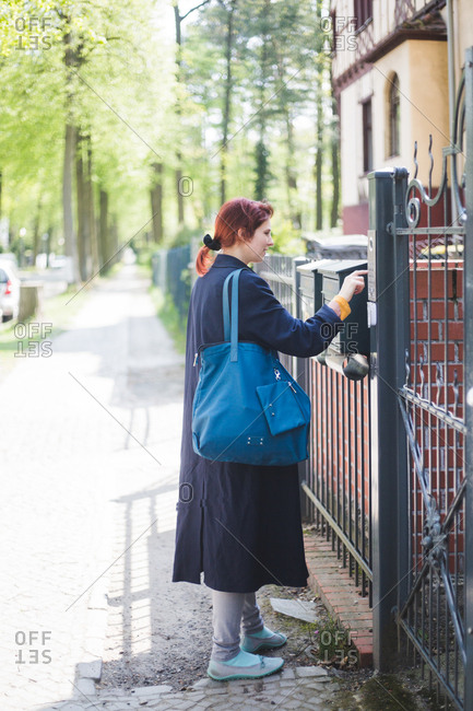 Full length of woman entering password on security system over gate