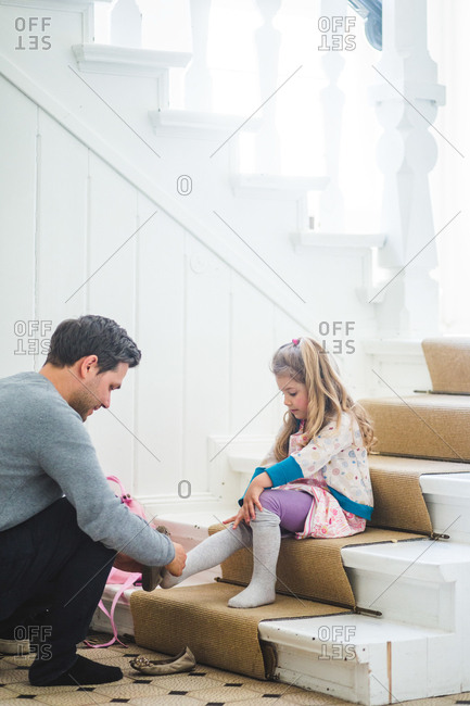 Father assisting schoolgirl wearing shoes while sitting on steps at home