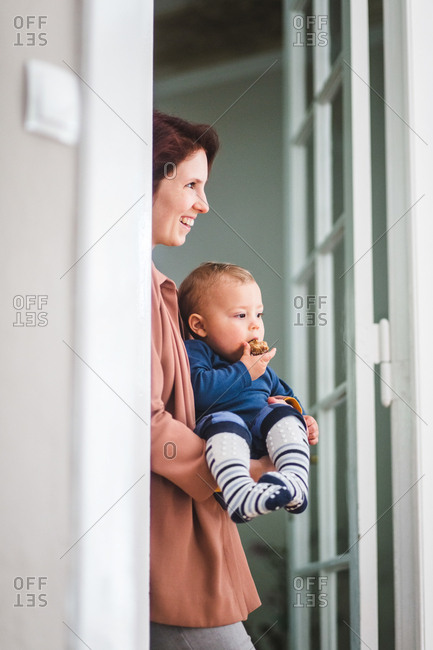 Smiling mother with son looking away while standing at home entrance