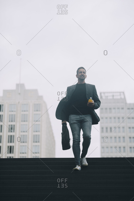 Businessman moving on steps at subway against clear sky