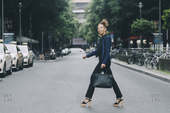 Side view of businesswoman crossing street in city