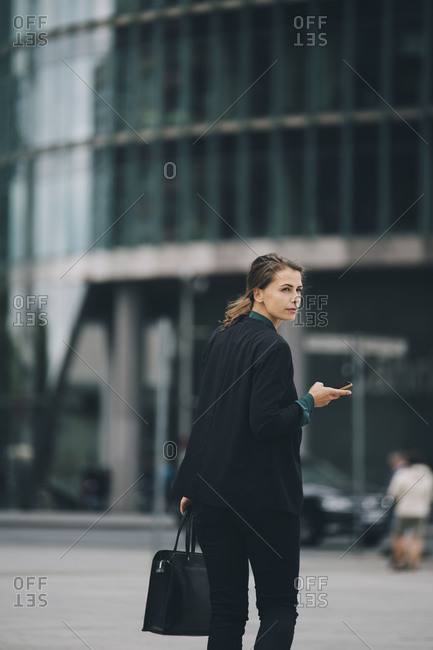 Businesswoman looking over shoulder while walking on street in city