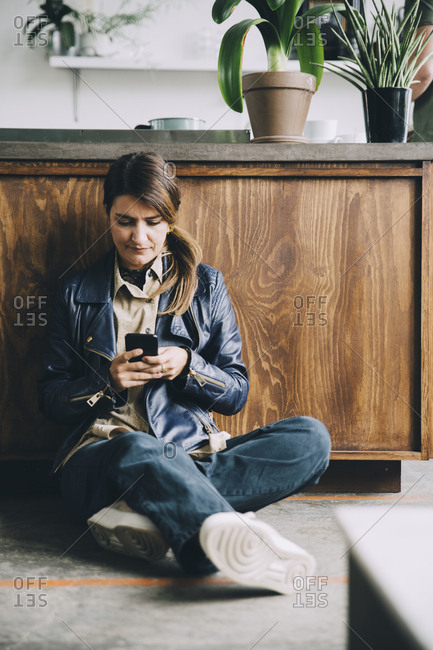 Full length of creative businesswoman using mobile phone while sitting against kitchen island in office