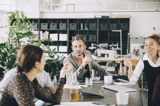 Creative business people discussing at table in office