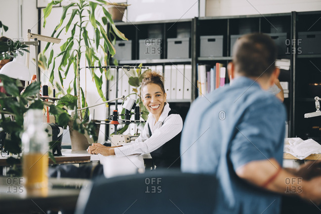 Smiling businesswoman looking at male colleague while working in creative office