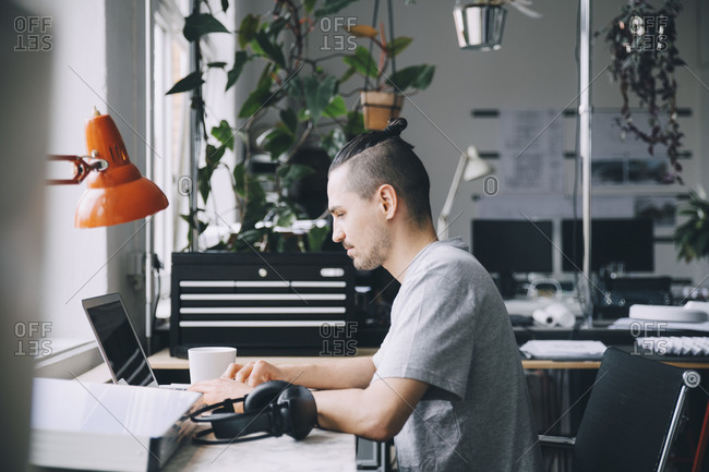 Side view of male hipster using laptop at desk in creative office