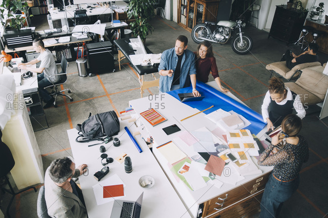 High angle view of creative businessmen and businesswomen working at table in office