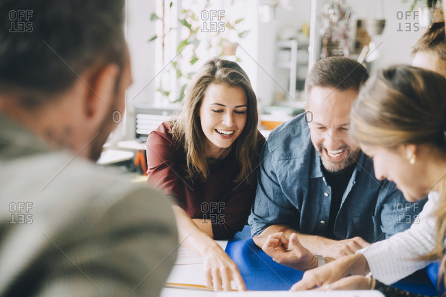Cheerful male and female entrepreneurs at table during meeting in creative office