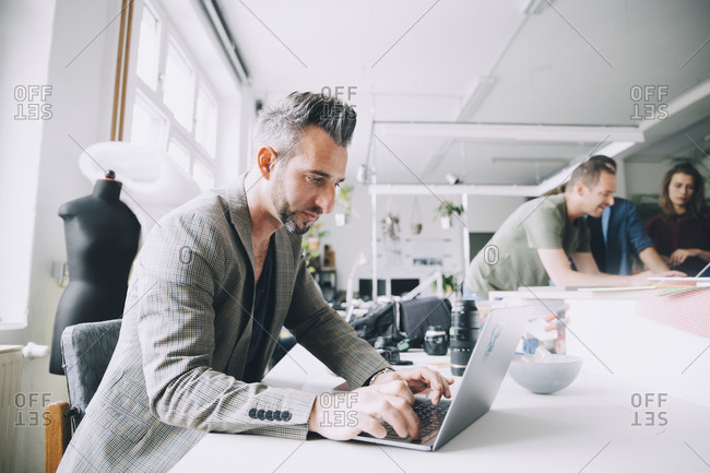 Confident businessman using laptop at desk in creative office