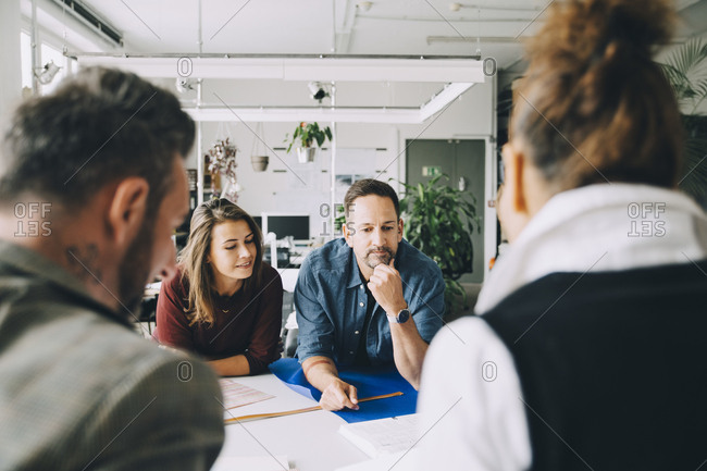 Confident male and female entrepreneurs at table during meeting in creative office