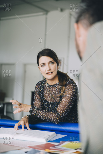 Confident businesswoman explaining male colleague during meeting in creative office