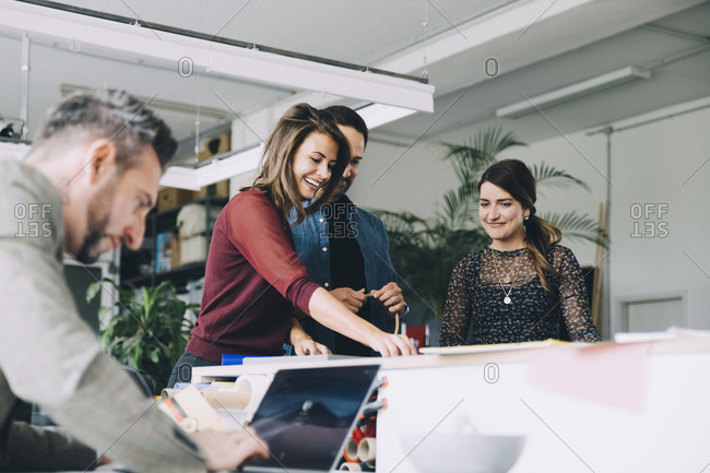 Smiling businesswoman working with colleagues while businessman using laptop in creative office