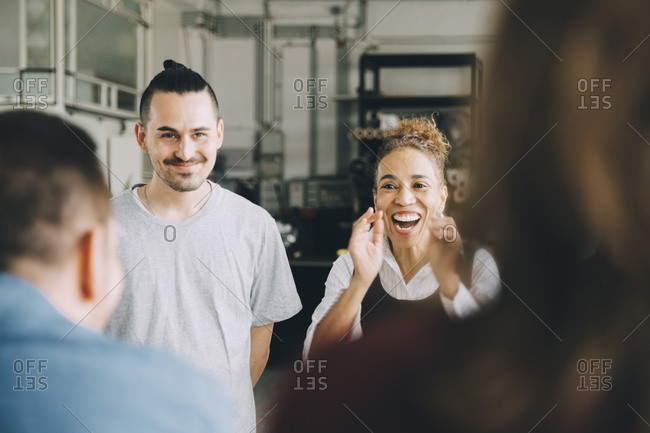 Happy businesswoman and businessman with colleagues in creative office