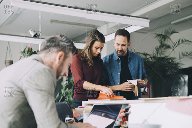 Businessman and businesswoman discussing while male colleague working on laptop in creative office