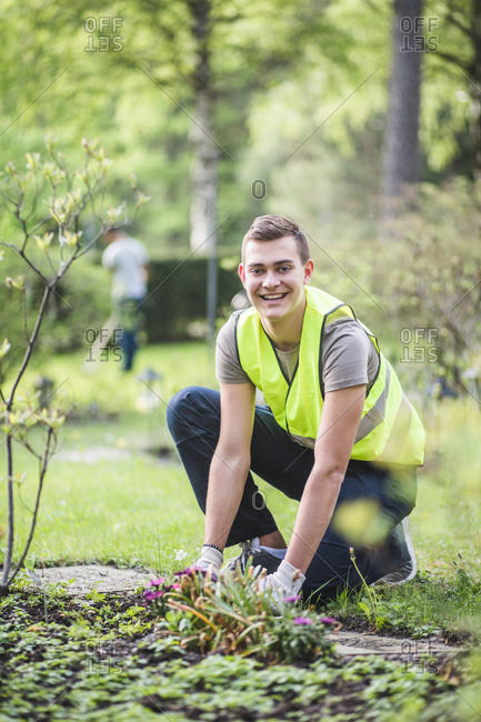 Full length portrait of smiling young man planting at garden