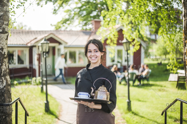 Portrait of confident young female waitress smiling while holding serving tray against outdoor cafe