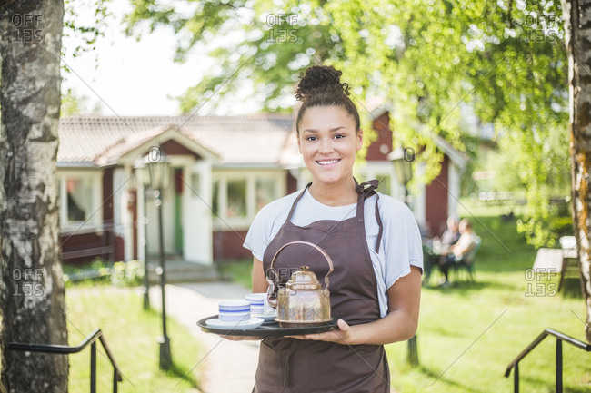 Portrait of smiling young waitress holding serving tray at restaurant