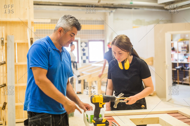 Male instructor teaching female trainee at workbench in illuminated workshop
