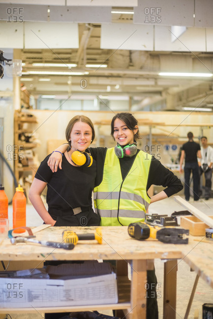 Portrait of smiling young female coworkers standing with arm around at workbench