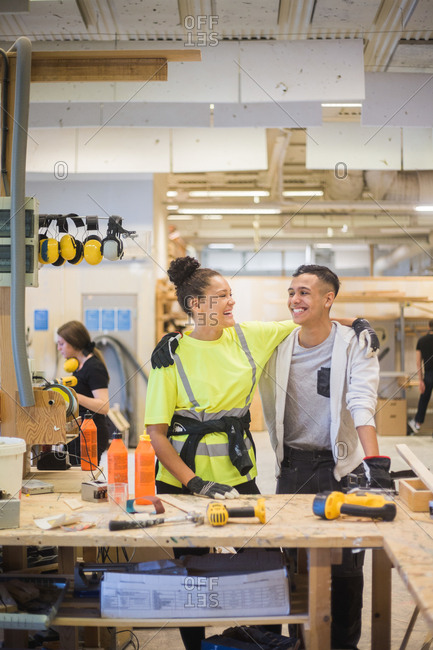 Cheerful female trainee standing with arm around male coworker at workbench