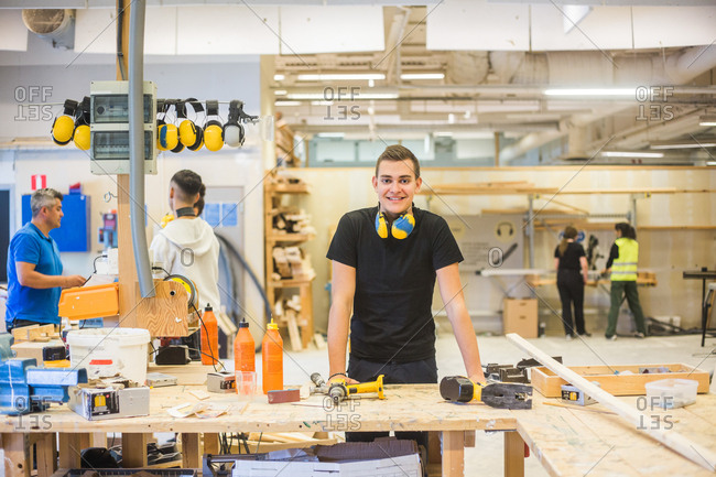 Portrait of confident young trainee standing at workbench at illuminated workplace