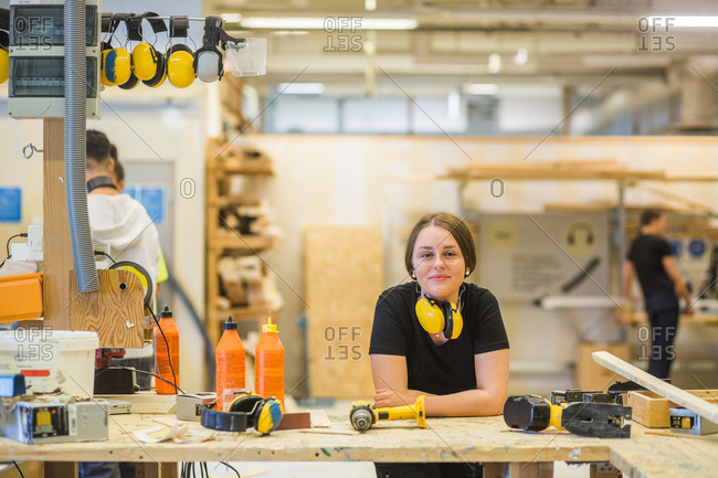 Portrait smiling young female carpentry trainee leaning on workbench with power tools at illuminated workshop