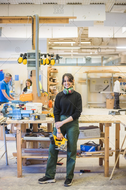 Full length portrait of smiling young female trainee holding power tool while standing in workshop