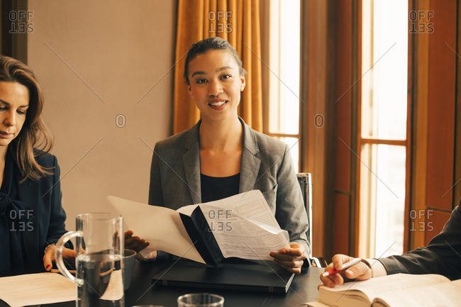 Portrait of smiling female legal professional with document at conference table in office