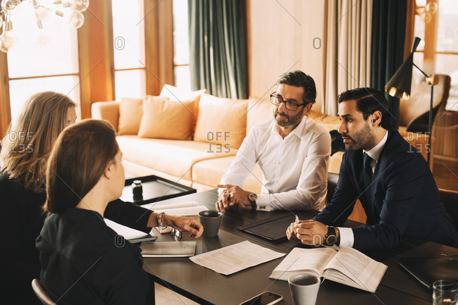 Male and female legal coworkers planning in meeting at board room