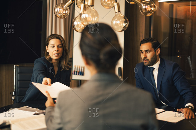 Mid adult lawyer with colleague giving document to advisor in office