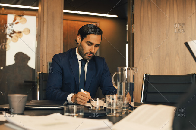Serious male financial advisor reviewing documents at legal office