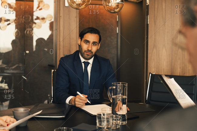 Portrait of confident mid adult lawyer with documents at conference table in law office
