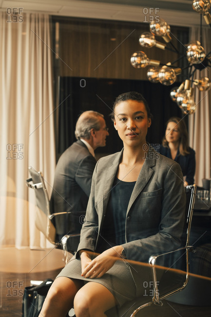 Portrait of confident female advisor with colleagues in background at office