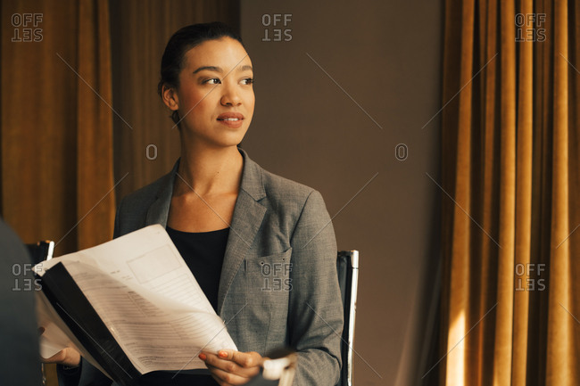 Thoughtful female lawyer with document looking away at law office