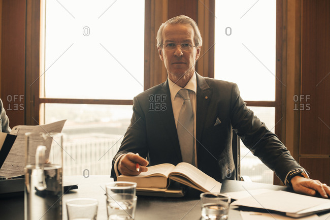 Portrait of confident mature lawyer with book at conference table in office