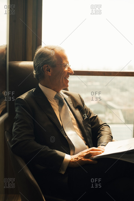 Smiling mature lawyer with documents looking through window at office