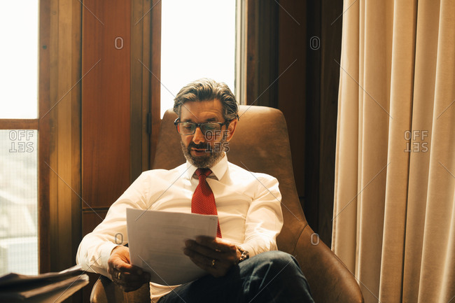 Male financial advisor reading documents at legal office