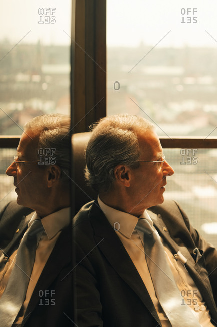 Thoughtful lawyer sitting by window at law office