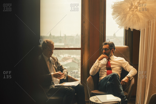 Male financial advisors discussing while sitting against window at law office