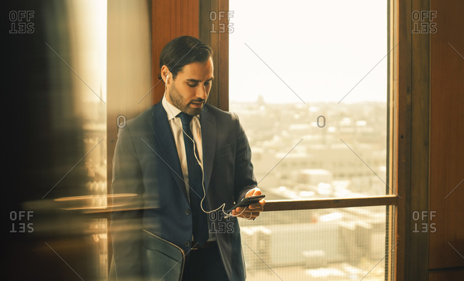 Mid adult legal professional using smart phone while standing against window at law office