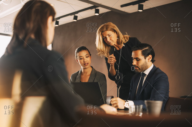 Mature female professional discussing with lawyers at office